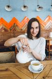 Woman pours green tea from a teapot into a Cup in a cafe stock image