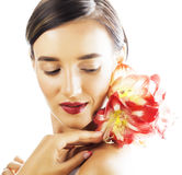 Young pretty brunette woman with red flower amaryllis close up i Stock Photography