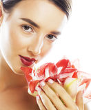 Young pretty brunette woman with red flower amaryllis close up i Royalty Free Stock Image