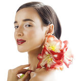 Young pretty brunette woman with red flower amaryllis close up isolated on white background. Fancy fashion makeup Stock Photography