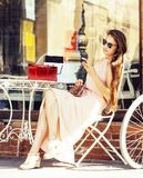 Young pretty brunette woman after shopping sitting at cafe outside on street smiling Stock Photo