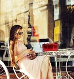 Young pretty brunette woman after shopping sitting at cafe outside on street smiling. Wearing dress and sunglasses, summer time Royalty Free Stock Image