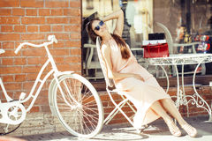 Young pretty brunette woman after shopping sitting. At cafe outside on street smiling, wearing dress and sunglasses, summer time Royalty Free Stock Photos
