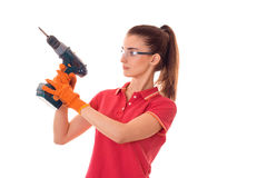 Young pretty brunette woman in uniform makes renovation with drill in her hands looking away isolated on white Stock Images