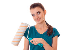 Young pretty brunette woman in uniform makes renovation with paint roller in her hands smiling on camera isolated on Royalty Free Stock Photography