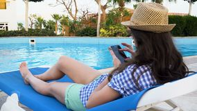 Young pretty brunette woman wearing hat lies on a lounger by the pool and uses mobile phone. 3840x2160 4k.  stock footage