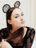 Young pretty brunette woman wearing sexy lace mouse ears, laying waiting dreaming in bed Stock Image