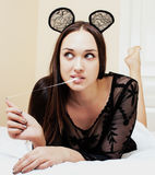 Young pretty brunette woman wearing sexy lace mouse ears, laying waiting dreaming in bed Royalty Free Stock Photos