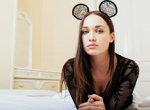 Young pretty brunette woman wearing sexy lace mouse ears, laying waiting dreaming in bed Stock Images