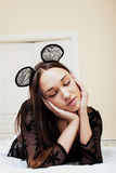 Young pretty brunette woman wearing sexy lace mouse ears, laying waiting dreaming in bed Stock Photos