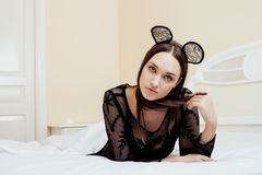 Young pretty brunette woman wearing sexy lace mouse ears, laying waiting dreaming in bed Stock Photography