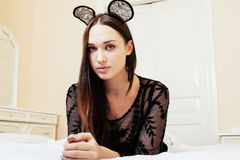Young pretty brunette woman wearing sexy lace mouse ears, laying Stock Images