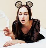 Young pretty brunette woman wearing lace mouse ears, laying Stock Image