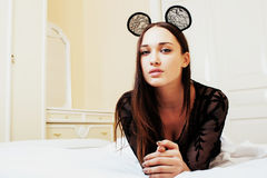 Young pretty brunette woman wearing lace mouse ears, laying Royalty Free Stock Photography