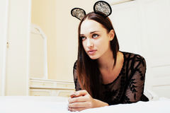 Young pretty brunette woman wearing lace mouse ears, laying Royalty Free Stock Images
