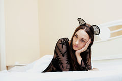 Young pretty brunette woman wearing sexy lace mouse ears, laying waiting dreaming in bed Royalty Free Stock Images
