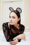 Young pretty brunette woman wearing sexy lace mouse ears, laying waiting dreaming in bed Royalty Free Stock Image
