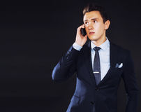 Young pretty business man standing on black background, modern h Stock Photo