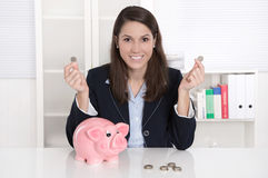 Young pretty business woman count money - coins with a piggy ban Royalty Free Stock Images