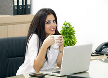 Young pretty business woman having coffee in office Stock Photography