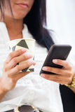 Young pretty business woman with mobile phone in her office. Stock Photography
