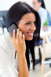 Young pretty business woman with mobile phone in her office. Stock Image