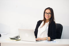 Young pretty business woman with notebook laptop in the office Stock Photography