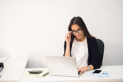 Young pretty business woman with notebook laptop in the office Royalty Free Stock Image