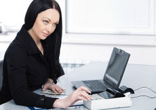 Young pretty business woman with notebook in the office Royalty Free Stock Photo