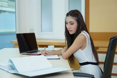 Young pretty business woman with notebook in the office.  Stock Images