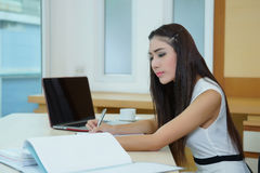 Young pretty business woman with notebook in the office Stock Photos