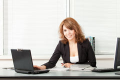 Young pretty business woman in the office Royalty Free Stock Image