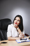Young pretty business woman working at her office. Adult young pretty business woman working at her office Royalty Free Stock Images