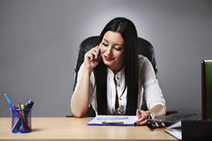 Young pretty business woman working at her office. Adult young pretty business woman working at her office Royalty Free Stock Photography