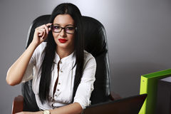 Young pretty business woman working at her office. Adult young pretty business woman working at her office Royalty Free Stock Image