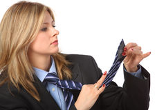 Young pretty businesswoman looks on tie Royalty Free Stock Image