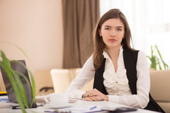 Young pretty businesswoman sitting at workplace in office Royalty Free Stock Photos