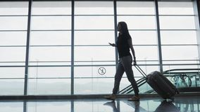 Young Pretty Businesswoman Using a Smartphone at Airport While Waiting Her Queue For Registration, Travelling Concept. 4K stock footage