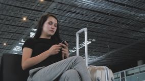 Young Pretty Businesswoman Using a Smartphone at Airport While Waiting Her Queue For Registration, Travelling Concept. 4K stock video footage