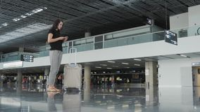 Young Pretty Businesswoman Using a Smartphone at Airport While Waiting Her Queue For Registration, Travelling Concept. 4K stock video