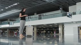 Young Pretty Businesswoman Using a Smartphone at Airport While Waiting Her Queue For Registration, Travelling Concept stock video footage