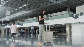 Young Pretty Businesswoman Using a Smartphone at Airport While Waiting Her Queue For Registration, Travelling Concept. 4K Stock Photos