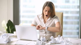 Young pretty businesswoman yawning, checking time, working extra after hours stock video
