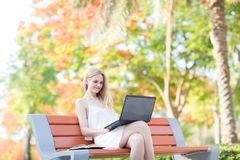 Beautiful woman sitting on a park bench using a laptop. Colorful trees in the background stock images