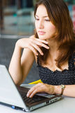 Young pretty caucasian lady using laptop outdoors Royalty Free Stock Image