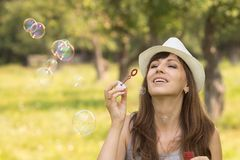Young pretty caucasian woman having fun with blowing bubbles Stock Photography