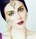 Young pretty caucasian woman like indian in ethnic jewelry close up on white, bridal makeup Stock Photos