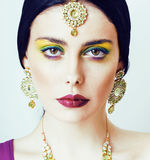 Young pretty caucasian woman like indian in ethnic jewelry close up on white, bridal makeup Royalty Free Stock Photo