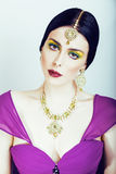 Young pretty caucasian woman like indian in ethnic jewelry close up on white, bridal makeup Stock Image