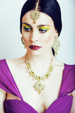 Young pretty caucasian woman like indian in ethnic jewelry close up on white, bridal makeup Stock Photography